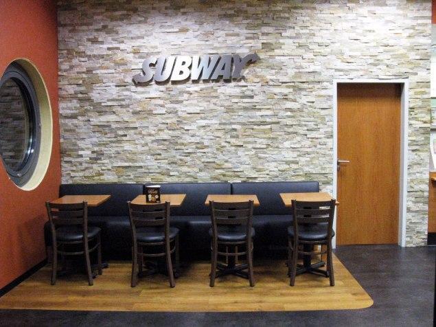 Eingangsbereich, Sitzbank mit vier Tischen. Steinwand mit Subway Schriftzug